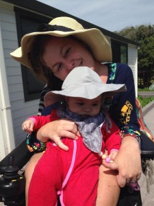 Photo of mom in power wheelchair holding infant daughter. Both sitting outside wearing sun hats.