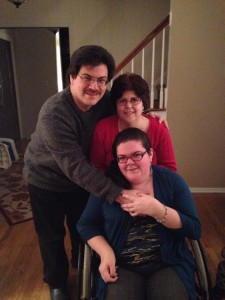 Photo of mother, daughter who is sitting in a wheelchair, and father. All with their arms around each other