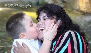 Photo of mother and son. Son is kissing mother on the cheek, the mother is smiling and hugging son