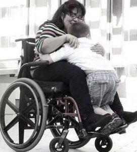 Photo of mother sitting in manual wheelchair with her son standing on her foot petals leaning in. They are hugging one another.