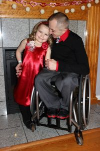 Photo of father, sitting in his wheelchair, with his arm around his young daughter. Both are dressed formally.