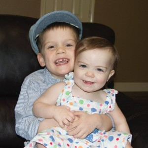 Two young white children sitting together smiling .