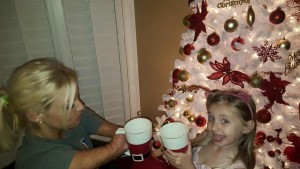 Woman in wheelchair and young girl holding Christmas mugs in front of Christmas tree