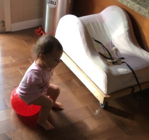 Photo of baby seat on top of dolly that has wheels underneath. Baby is sitting on a ball next to it,