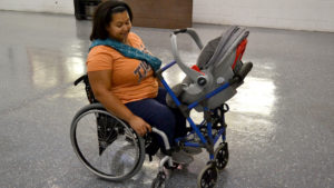 Photo of woman in wheelchair with stroller attached