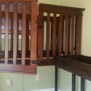 Accessible wooden crib, door is cut down middle and open. Wooden changing table also shown