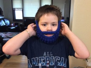 Young boy wearing knit hat with fake mustache and beard