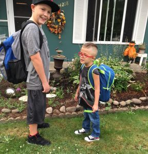 Two young boys standing outside of home wearing backpacks
