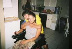 Latina woman in a power wheelchair with son standing behind with his arm wrapped around her.