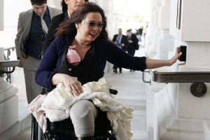 Duckworth holding baby and pushing button to open door