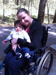 Mother sitting in a wheelchair while holding her child in a wooded setting