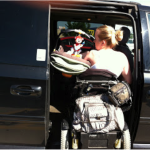 photo of mother unloading baby from car with one arm