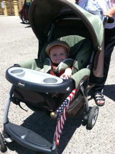 6 month old white baby boy in large green stroller with canopy and tray. Small American flag sticking out of stroller.