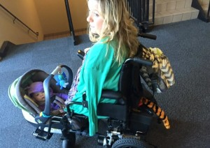 White woman with no legs and one arm in power wheelchair with baby carseat/carrier wedged between wheelchair footrests.