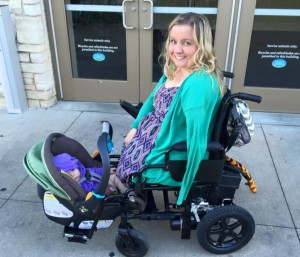 White woman with no legs and one arm smiling at camera in power wheelchair with baby carseat/carrier snugly wedged between wheelchair footrests. Baby is facing the woman.