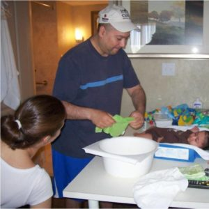 Photo of baby getting sponge bath on changing table. Man is standing, washing baby. Woman in wheelchair looks on.