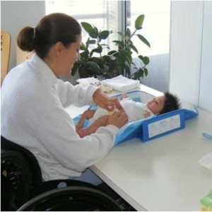 Photo of mother in wheelchair changing baby laying on a desk