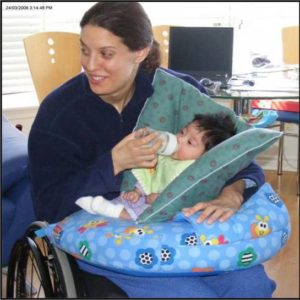 Photo of mother in wheelchair giving bottle to baby who is propped up with pillows