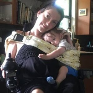 Photo of mother in wheelchair holding son with ring sling
