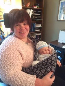 Woman in power wheelchair holding baby in sling carrier