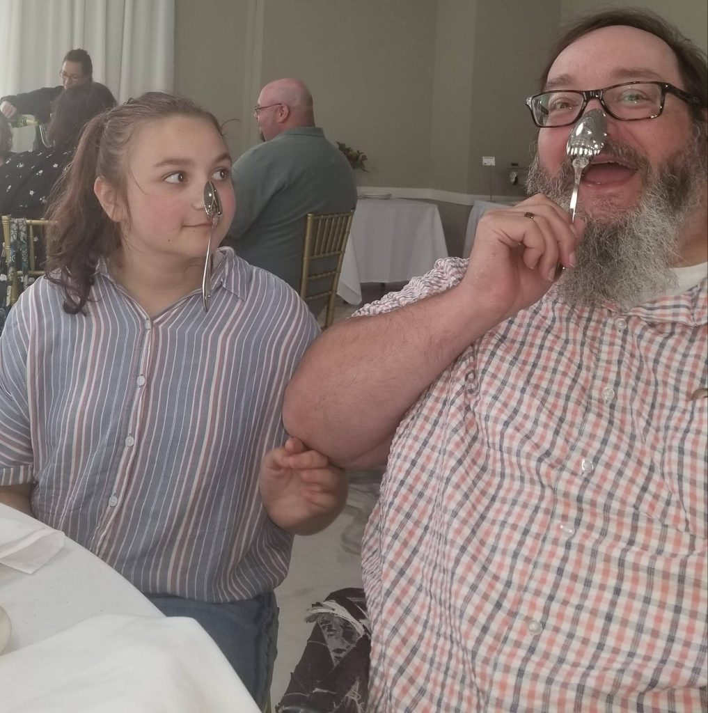 Father and daughter balancing spoons on their noses