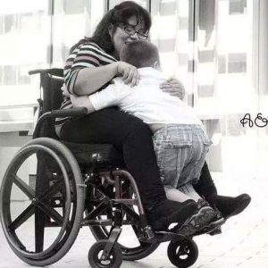 Black and white photo of woman in wheelchair holding young boy