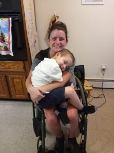 Woman in wheelchair holding young boy