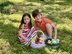 Two white schooled children with brown hair, dressed in colorful spring clothes on green grass with Easter baskets full of eggs in front of them