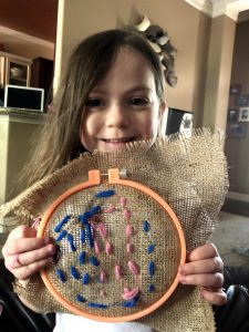 Brown haired 5 year old white girl with brown hair, smiling while holding a blue and pink needlepoint craft project