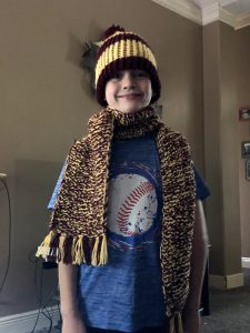 9 year old white boy wearing a knit hat and scarf in maroon and gold yarn colors