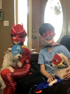 Author's school aged children, one boy and one girl, white with brown hair dressed in red and blue superhero costumes, each holding a mixed breed small white dog also wearing superhero marks. Children are smiling