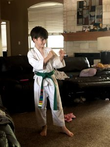 9 year old white boy with brown hair dressed in white martial arts outfit with a green belt in a taikwondo punch stance in a living room setting