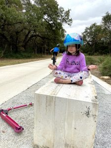 Young white girl with brown hair and purple outfit wearing Frozen themed helmet in a meditation pose sitting on concrete block next to paved bike path with eyes closed. Older white boy on bike in background from the back.