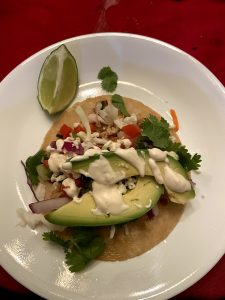 White dinner plate with tortilla covered in fish, cilantro, avocado, pico de gallo, cheese and slaw