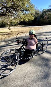 Author sitting on hand cycle, wearing green helmet smiling